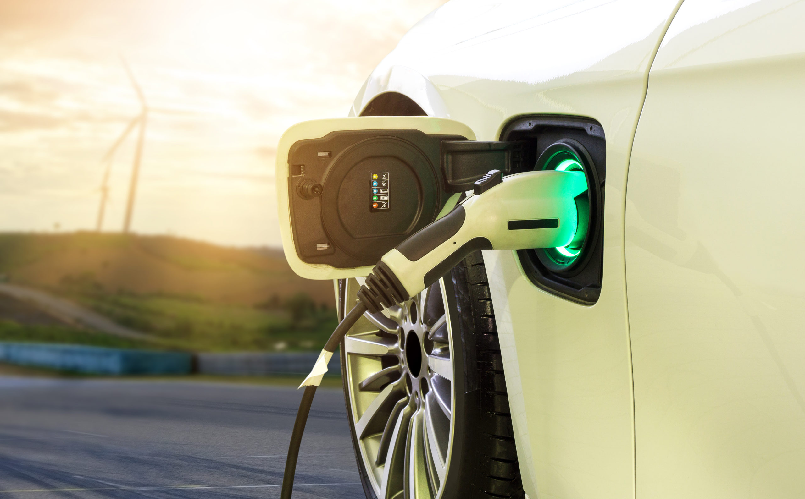 zero emissions electric vehicle being charged with wind turbines in the background