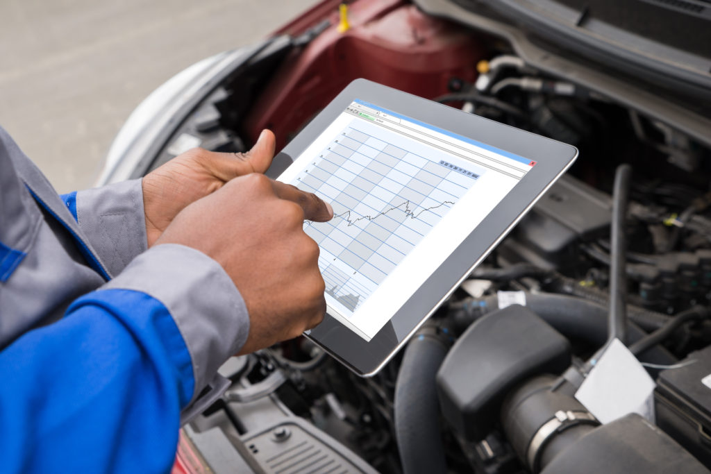man using a tablet to do maintenance checks next to an open car engine